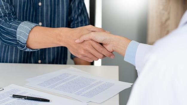 Médecin attrayant et patient se serrant la main pour l'encouragement et l'empathie, les soins de santé et l'assistance, concept médical.