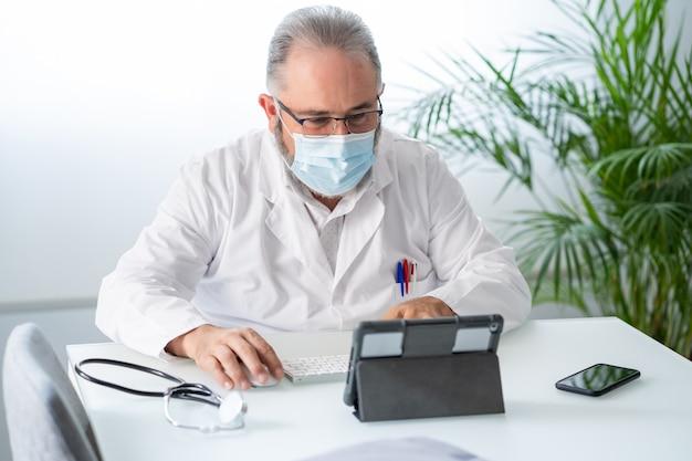 Médecin ayant une vidéoconférence avec sa tablette dans son bureau et son masque facial