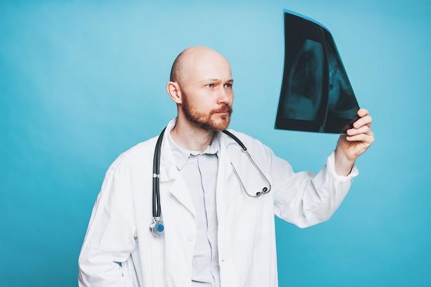 Médecin barbu chauve amical attrayant en regardant la radiographie isolé sur fond bleu