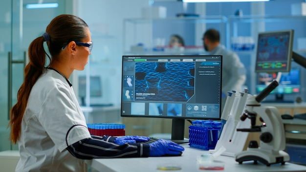 Médecin biologiste vérifiant les informations adn en tapant sur pc dans un laboratoire moderne équipé. des scientifiques examinant l'évolution des vaccins dans un laboratoire médical à l'aide d'outils chimiques de haute technologie pour la recherche scientifique.
