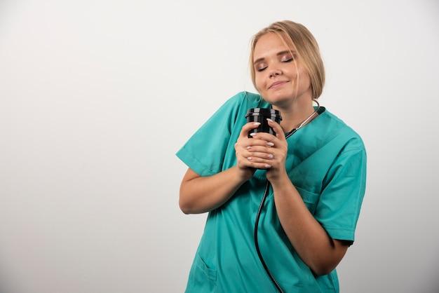 Médecin blonde posant avec une tasse de café sur un mur blanc.