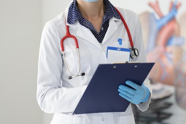 Médecin en blouse blanche et gants tient le presse-papiers.