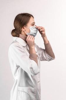 Un médecin en blouse blanche montre comment porter un masque médical
