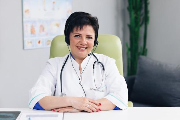 Un médecin en blouse blanche porte un casque regardant à l'avant et sourit dans le bureau de l'hôpital.