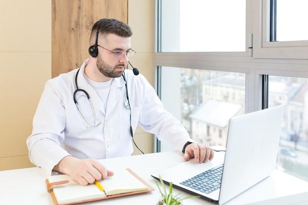 Médecin en blouse médicale blanche et casque faisant une conférence téléphonique sur un ordinateur portable