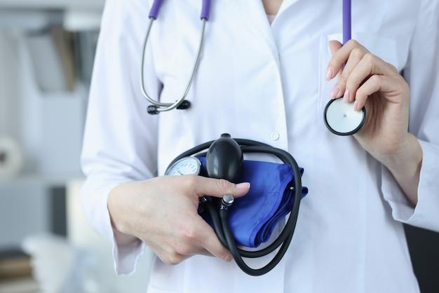 Médecin cardiologue tenant gros plan tonomètre et stéthoscope. concept de contrôle de la pression artérielle