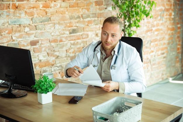 Médecin caucasien consultant pour patient, expliquant la recette du médicament, travaillant dans le cabinet