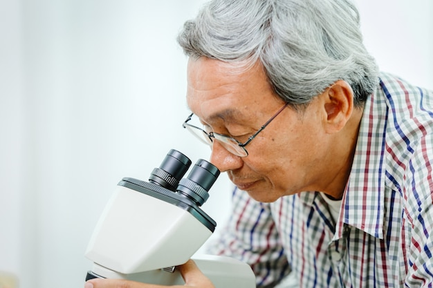 Médecin chinois asiatique à la recherche de microscope pour la science médicale des virus et la recherche en laboratoire hospitalier