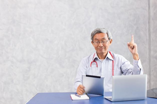 Médecin chinois utilisant une tablette informatique avec une pensée réfléchie trouver une solution anti-virus a trouvé quelque chose et une action de créativité.