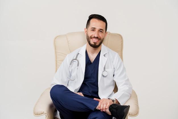 Médecin chirurgien arabe en robe médicale avec sièges phonendoscope et sourire dans un fauteuil