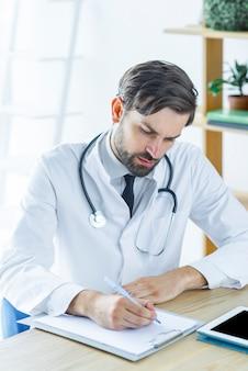 Médecin ciblé prenant des notes au bureau
