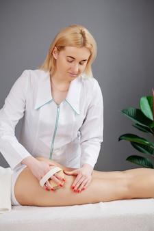 Un médecin de la clinique donne à la femme un massage anticellulite