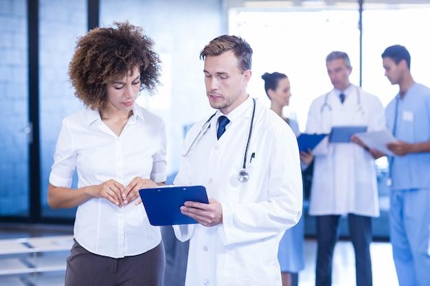 Médecin et collègue examinant un rapport médical et discutant