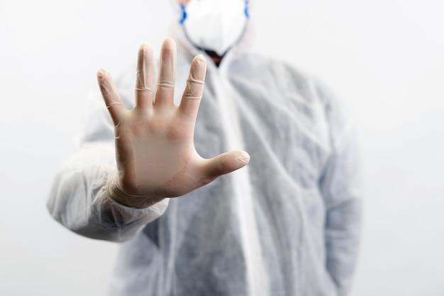 Médecin avec combinaison de protection et masque montrant un panneau d'arrêt avec une main.