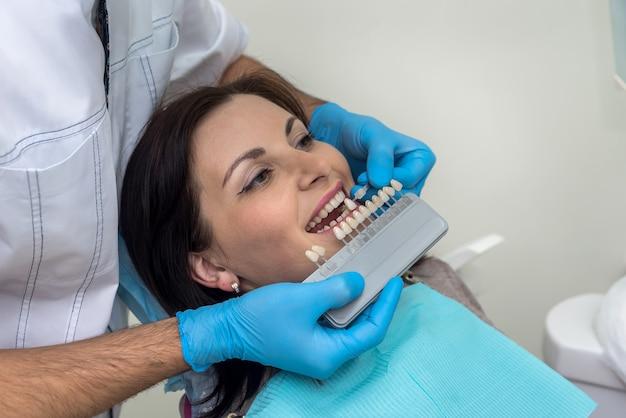 Médecin comparer les dents de la femme avec un échantillonneur en dentisterie