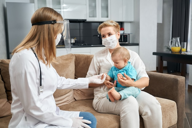 Médecin compétent en masque examinant bébé à la maison