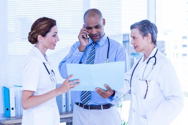 Médecin concentré montrant le dossier à ses collègues tout en appelant à l'hôpital