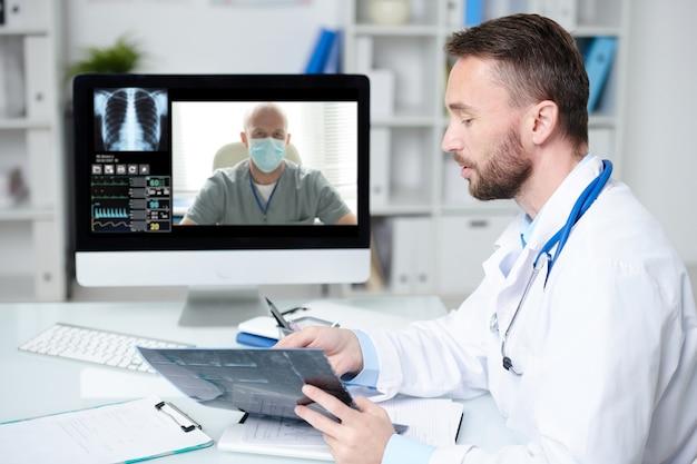 Médecin confiant en blouse blanche assis devant un écran d'ordinateur et pointant sur la radiographie du patient lors d'une consultation en ligne avec un collègue