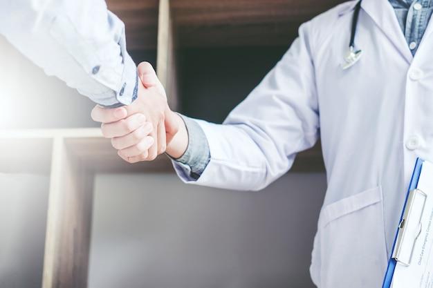 Médecin confiant serrant la main avec les patients parlent à l'hôpital
