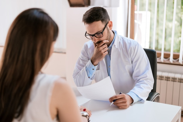 Médecin consultant et examinant la santé de la patiente dans une clinique médicale.