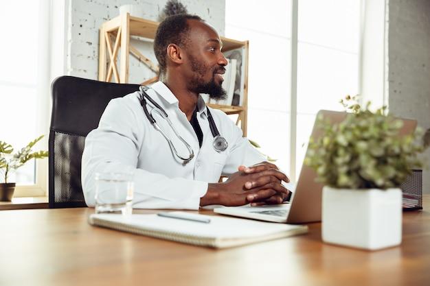 Médecin consultant pour le patient, travaillant avec un ordinateur portable
