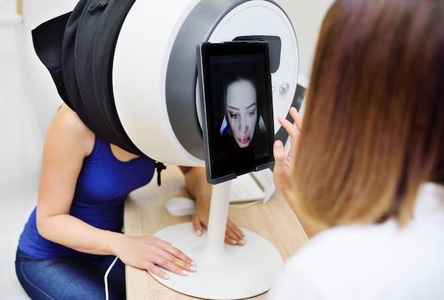 Le médecin cosmétologue analyse la peau du visage d'une jolie jeune femme