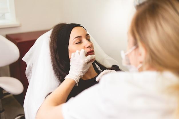 Médecin cosmétologue donne une injection de menton pour le patient