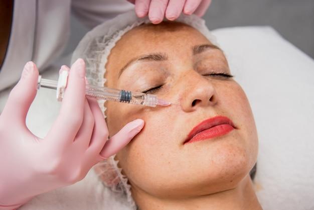 Le médecin cosmétologue effectue la procédure d'injections faciales. jeune femme dans un salon de beauté.