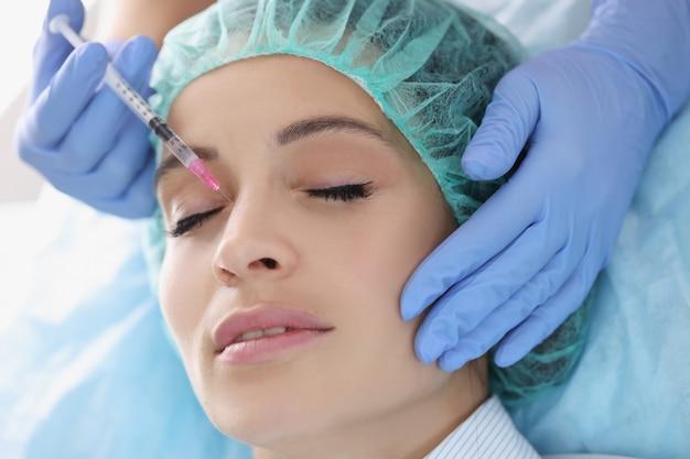 Médecin cosmétologue faisant l'injection dans la zone nasale d'une patiente en clinique. concept de correction de correction de bosse de forme de nez