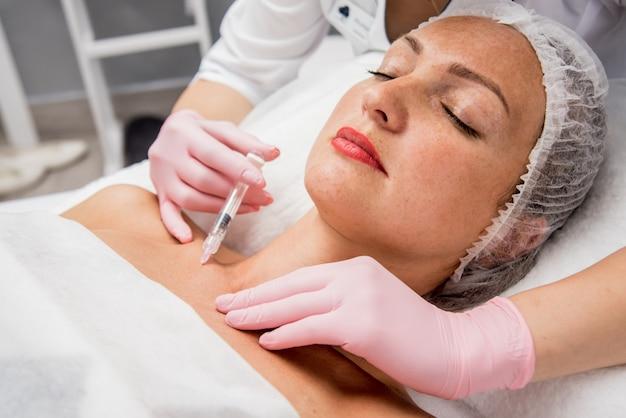 Le médecin cosmétologue fait la procédure d'injections de décolleté. jeune femme dans un salon de beauté.