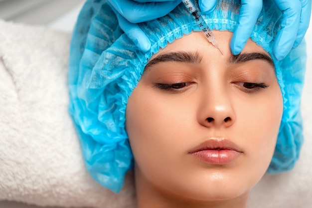 Le médecin cosmétologue réalise la procédure d'injections faciales rajeunissantes pour resserrer et lisser les rides sur la peau du visage d'une femme dans un salon de beauté. cosmétologie soins de la peau