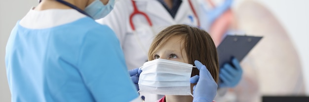 Médecin en costume bleu et masque de protection a mis un masque de protection sur le visage de la fille.