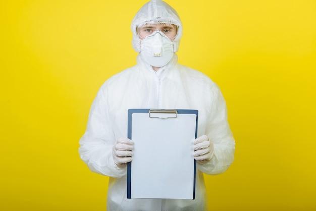 Médecin en costume de protection individuelle (epi) avec un presse-papiers sur fond jaune