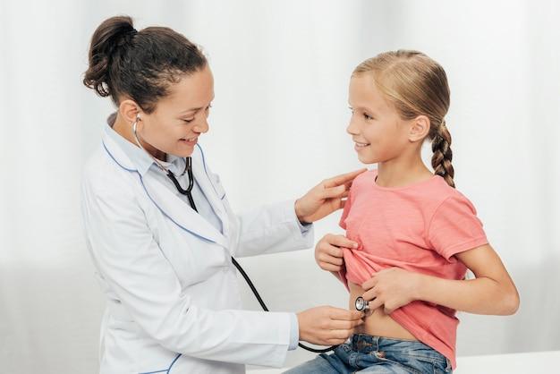 Médecin coup moyen vérifiant l'abdomen de la jeune fille