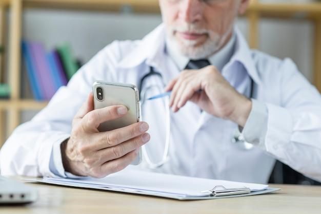 Médecin des cultures utilisant le smarthone au bureau