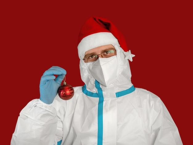 Médecin dans une combinaison antivirale de protection et bonnet de noel tient un ballon de noël