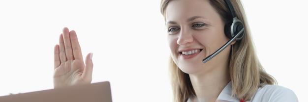 Médecin dans les écouteurs avec microphone agitant sa main à l'écran du portable
