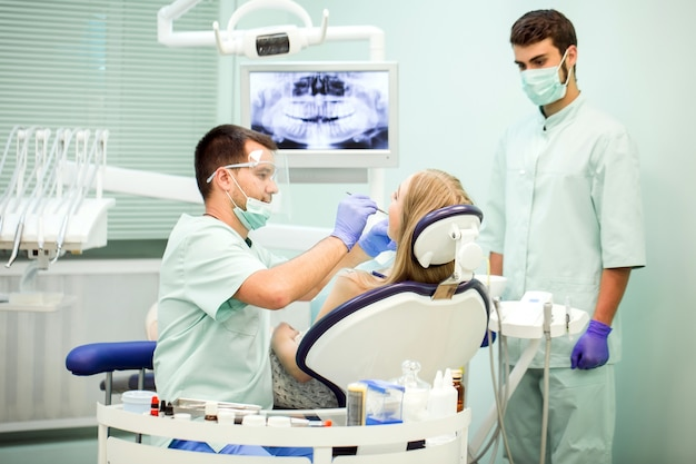 Médecin dentiste avec un assistant dans une clinique dentaire.