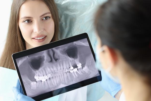 Médecin dentiste tenant une tablette numérique avec une radiographie des dents devant le patient