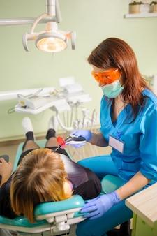 Médecin dentiste tient une lampe photopolymère de dentiste traitant un patient en clinique