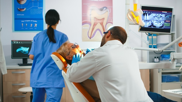 Médecin dentiste travaillant dans une unité dentaire avec infirmière et patient senior. orthodontiste parlant à une femme assise sur une chaise stomatologique pendant que l'infirmière prépare des outils pour l'examen dans une clinique moderne