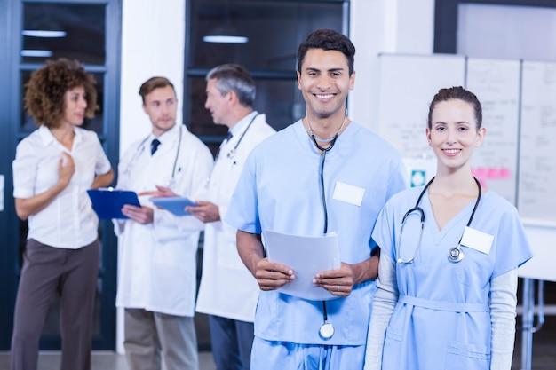 Médecin détenant un rapport médical et souriant pendant que ses collègues discutent en arrière-plan