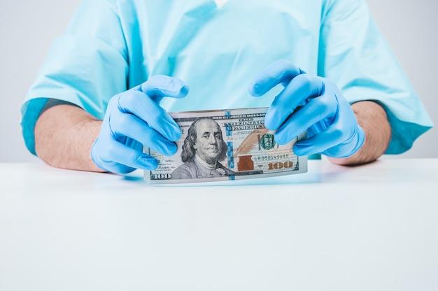 Le médecin détient des billets de cent dollars. le concept de corruption en médecine