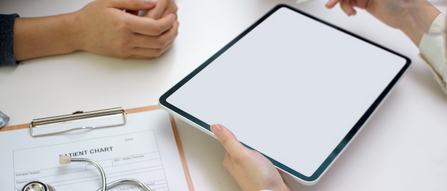Médecin diagnostiquer le patient avec une tablette écran vierge, un dossier patient et un stéthoscope dans la salle d'examen