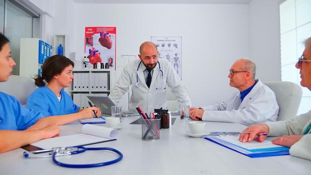 Médecin discutant avec le personnel médical dans la salle de conférence de l'hôpital portant une blouse de laboratoire. thérapeute expert de la clinique discutant avec des collègues de la maladie, du diagnostic des problèmes de traitement des patients