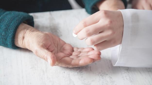Médecin donnant un comprimé à une femme âgée