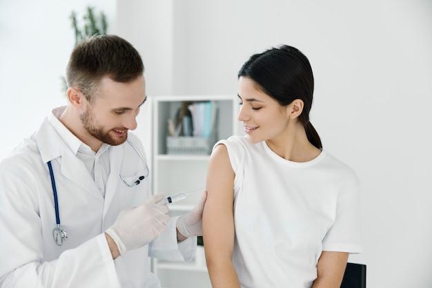 Médecin donnant un coup de feu à une femme à l'hôpital épidémique de vaccination de l'épaule