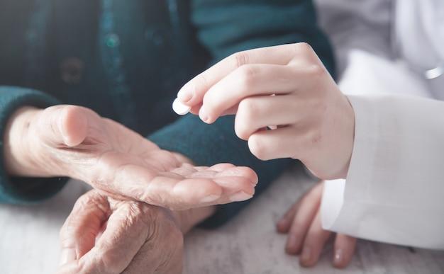 Médecin donnant la pilule à une femme âgée. santé, médecine, soins