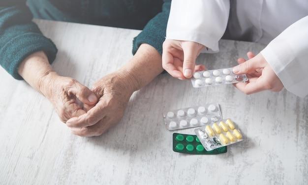 Médecin donnant des pilules à une femme âgée