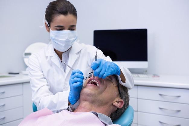 Médecin donnant un traitement dentaire au patient à la clinique